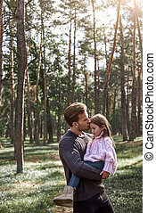 A father kisses his little pretty daughter in forest