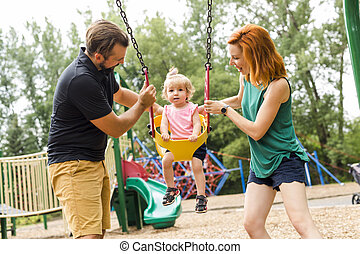 Father, mother with their daughter have fun on a swing