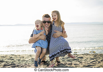Father playing with two daughter at beach in a sunny day.