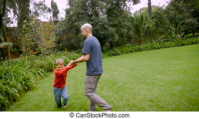 A father spins his 5 year old son around in circles on the grass - slowmo