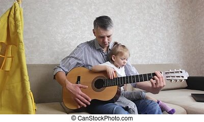 A father teaches his young daughter to play the guitar