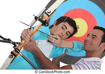 A father teaching his son how to shoot bow.