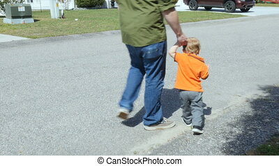 A father walking down a neighborhood streets holding his...