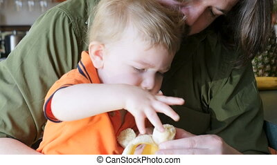 A father watches as his young son feeds himself a healthy...