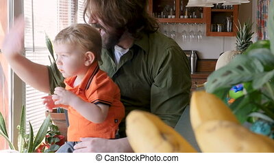 A father waves goodbye while his young son sits on his lap eating a snack