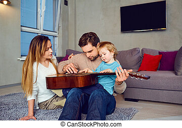 A father with a guitar sings a song for his family.