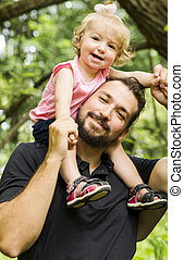 father with their cute little daughter on shoulder in meadow