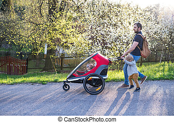 A father with toddler son pushing a jogging stroller outside in spring nature.