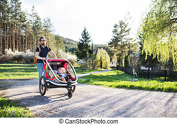 A father with two toddlers in jogging stroller on a walk outside in spring nature.