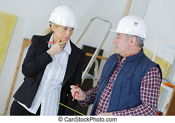 a female architect and a foreman discussing at construction site