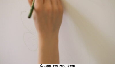 A female artist is painting on the wall in the apartment