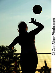 A female beach volleyball player serves during a competition in the late afternoon light.