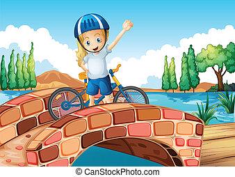 A female biker standing above the bridge