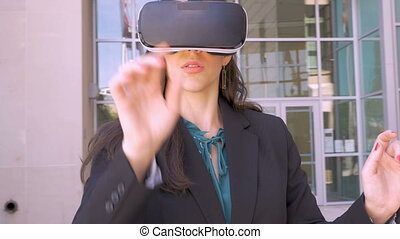 A female business executive virtual reality working with her VR goggles outside
