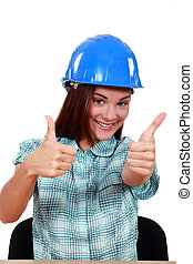 A female construction worker giving both thumbs up.
