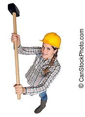 A female construction worker holding a sledgehammer.