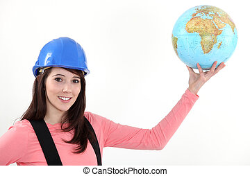 A female construction worker holding a globe.
