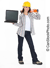 A female construction worker holding a laptop.