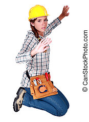 A female construction worker trapped in an invisible box.