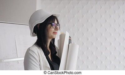 A female construction worker wearing white helmet and holding blueprints isolated