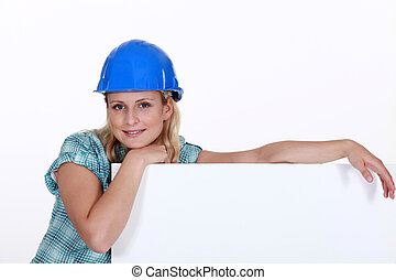 A female construction worker with a billboard.