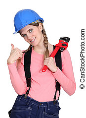 A female construction worker with a wrench.