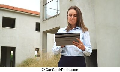 Female contractor in front of new building construction. - A...