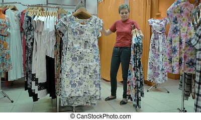 A female customer gathered many types of outfits - A...