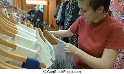 A female customer is browsing through the cloths. Video ...