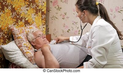 A female doctor listens to a patient with a phonendoscope at home. The man is lying on the couch.