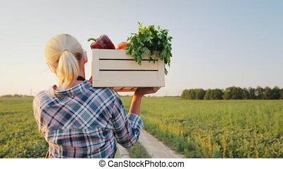 A female farmer with a box of fresh vegetables walks along...