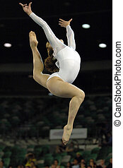A female gymnast leaps into the air during a floor routine...