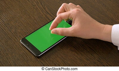 A female hand and a mobile phone with a green screen that lies on the table.