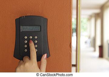 A female hand arming a burglar alarm system mounted on a...