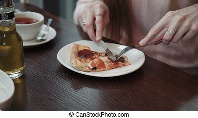 A female hand cuts and eats a slice of pizza, close-up shot. In a cafe, communication and friends