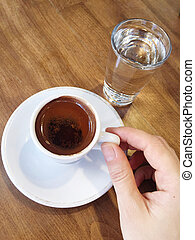 hand holding a cup turkish coffee on table