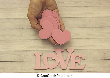 A female hand holds a wooden heart, the concept of love