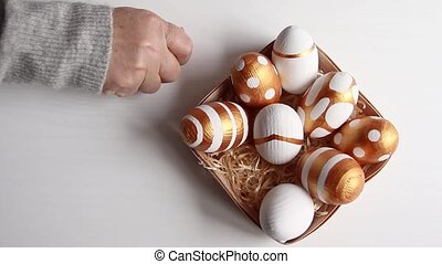 A female hand lays golden decorated Easter eggs in a wooden basket with hay on a white table. View from above. Happy easter concept.