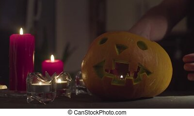A female hand places a candle in a Jack-o'-lantern. - Close...