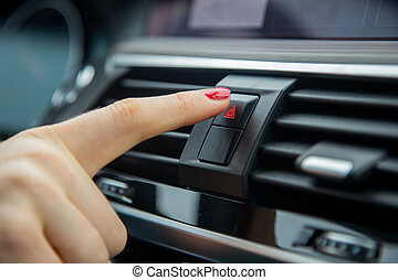 a female hand press the alarm light button on the dashboard of a car. close-up, soft focus, in the background car interior details in blur, side view