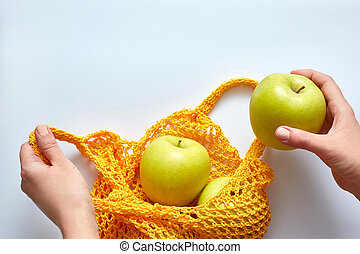 A female hand puts apples in a yellow string bag. The zero waste concept, top view.