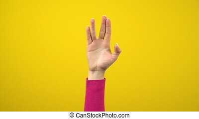 A female hand shows an alien greeting sign. Studio photography on an isolated yellow background. 4k