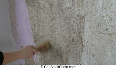 A female hand smears wallpaper glue on the wall with a...