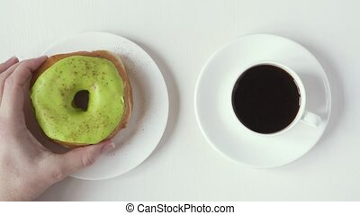 A female hand takes a donut and a cup of coffee, top view