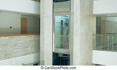 A female is standing in glass moving lift