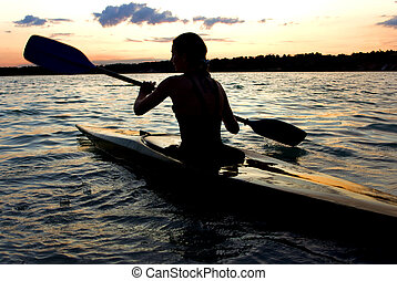 female kayaker - A female kayaker paddles across a lake...