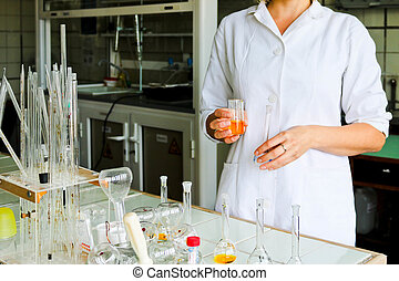 A female laboratory assistant, a doctor, a chemist, works with flasks, test tubes, makes solutions, medicines, mixes the ingredients in the laboratory. Laboratory assistant carries out the research