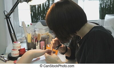 A female master makes manicure of hands girl