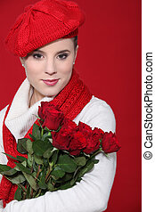 A female model holding a bunch of red roses.
