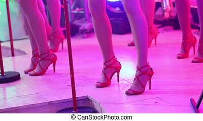 A female music band performs on stage, Beautiful Girls with saxophones on stage. Girl playing saxophone, beautiful female feet, women's legs in red high-heeled shoes